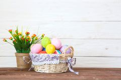 Colored easter eggs in the basket and spring flowers on wooden background. Greeting card Stock Images
