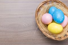 Easter eggs in the basket on wooden background royalty free stock photo
