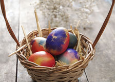 Colored easter eggs in basket on wooden table Stock Photos