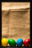 Colored Easter eggs in black metal frame, rustic background Stock Photography
