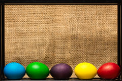 Colored Easter eggs in black metal frame, rustic background Stock Photo