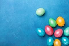 Colored Easter eggs on blue table top view. Holiday greeting card. Royalty Free Stock Photos