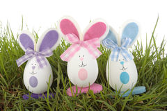 Colored easter  eggs bunnies on grass over white Stock Photo