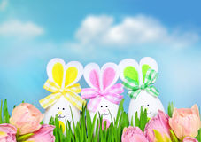 Colored easter eggs bunny on green grass and flowers. Colored easter eggs bunny on grass over blue sky background and flowers Royalty Free Stock Photography