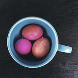 Colored easter eggs in ceramic cup on wooden background - vintag Royalty Free Stock Photos