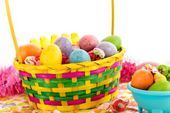 Colored Easter eggs, chicks, candy and basket Stock Image