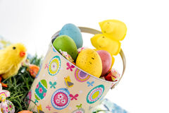 Colored Easter eggs, chicks, candy and bucket on grass Royalty Free Stock Images