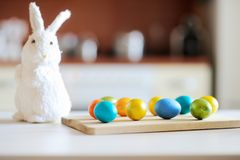 Colored Easter eggs and cute bunny on table on Easter day stock image