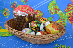 Colored Easter eggs and Easter cake in a wattled support on a colorful background Stock Photography