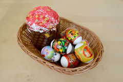 Colored Easter eggs and Easter cake in a wattled support on a light background Stock Photography