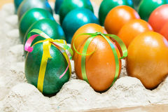 Colored Easter eggs in egg carton holder. Brightly colored decorated Easter eggs in egg carton holder, holiday background Stock Image