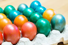 Colored Easter eggs in egg carton holder. Brightly colored Easter eggs in egg carton holder, holiday background Royalty Free Stock Images