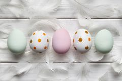 Colored Easter eggs and feathers on white background Stock Photos