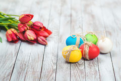Colored easter eggs, flower pot with green grass and beautiful tulips on wooden background. Stock Photos