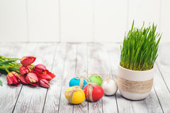 Colored easter eggs, flower pot with green grass and beautiful tulips on wooden background. Stock Photography
