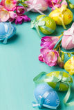 Colored Easter eggs and flowers on a turquoise table Royalty Free Stock Photo