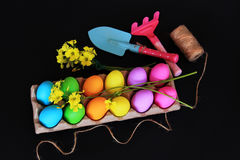 Colored Easter eggs with gardening tools, children gardening shovel, rake, rope and spring yellow flowers Royalty Free Stock Images
