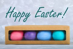 Colored Easter eggs in a gift box on a gray concrete background. royalty free stock photos