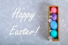 Colored Easter eggs in a gift box on a gray concrete background. royalty free stock images