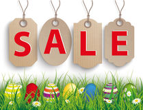 Colored Easter Eggs Grass Carton Price Stickers Sale. Green grass with colored easter eggs and 4 carton price stickers on the wooden background Stock Images