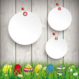 Colored Easter Eggs Grass 3 Circle Stickers Pins. Green grass with colored easter eggs and circle stickers on the wooden background Royalty Free Stock Image