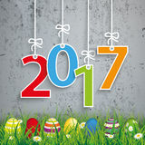 Colored Easter Eggs Grass 2017 Concrete. Green grass with colored easter eggs and numbers 2017 on the concrete background Stock Photos
