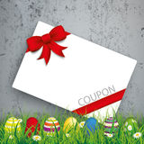 Colored Easter Eggs Grass Coupon Concrete. Green grass with colored easter eggs and coupon card on the concrete background Stock Photo