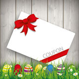 Colored Easter Eggs Grass Coupon. Green grass with colored easter eggs and coupon card on the wooden background Stock Image