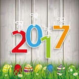 Colored Easter Eggs Grass 2017. Green grass with colored easter eggs and numbers 2017 on the wooden background Stock Photography