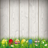 Colored Easter Eggs Grass. Green grass with colored easter eggs on the wooden background Royalty Free Stock Photography
