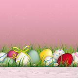 Colored Easter Eggs Grass Pink Background. Colored eggs with ribbon in the grass on the pink background Royalty Free Stock Images