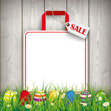 Colored Easter Eggs Grass Shopping Bag Sale. Green grass with colored easter eggs and shopping bag on the wooden background Royalty Free Stock Photo