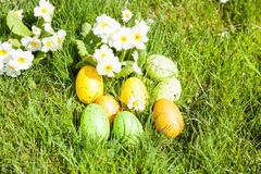 Colored Easter eggs hidden in flowers and grass Stock Photo