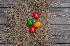 4 colored Easter eggs lays in the dry hay on the wooden aged board royalty free stock photos