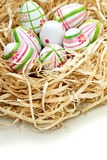 Colored Easter eggs into a nest Stock Images