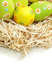 Colored Easter eggs into a nest from top Royalty Free Stock Photos