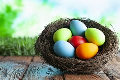 Colored Easter eggs in the nest on wooden table and nature background stock photo