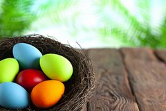 Colored Easter eggs in the nest on wooden table and nature background royalty free stock photos