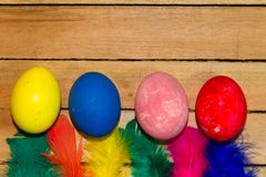 Eggs and feathers of easter colors on rustic wooden background stock photography