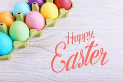 Colored Easter eggs in a pan, on a white wooden table. Text, happy easter stock photography