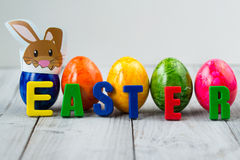 Colored Easter eggs with paper bunny and word easter made of magnet letters Stock Images