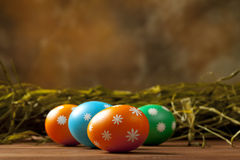 Colored Easter eggs, planks and decorative grass Royalty Free Stock Photography