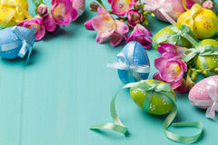 Colored Easter eggs with ribbons and flowers on a turquoise tabl Royalty Free Stock Images