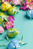 Colored Easter eggs with ribbons and flowers on a turquoise tabl Stock Photos