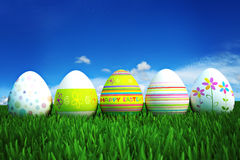Colored Easter eggs in a row. Row of Easter Eggs sitting on Fresh Green Grass Royalty Free Stock Photos