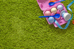 Colored easter eggs and spoons in a egg-box. On green background Royalty Free Stock Photos