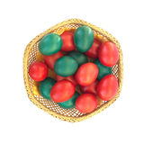 Colored Easter eggs in straw plate isolated on whi. Te background Stock Photo
