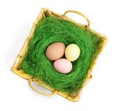 Colored easter eggs are in wattled basket Royalty Free Stock Photos