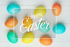 Colored Easter eggs on a white table, top view royalty free stock images