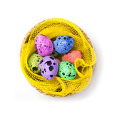 Colored Easter eggs in a wicker basket Royalty Free Stock Photography
